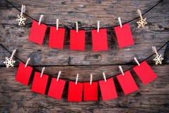 Många tomma röda etiketter framme av träbakgrund Royaltyfri Foto