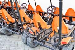 Många trendiga orange fyra-rullade sportcyklar, cirkuleringskort för familjsportrekreation och turism med ett hjul och pedaler royaltyfri foto