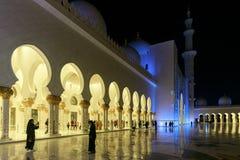 Många turister beundrar de härliga sikterna av Sheikh Zayed Grand Mosque, exponerade med blått ljus i aftonen royaltyfri foto