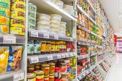 Många typer av på burk livsmedelsprodukter i supermarket royaltyfri bild