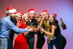 Många unga kvinnor och män som dricker på julpartiet royaltyfria foton