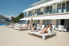 Många unga män och kvinnor vilar på området för sommar för hotell` s Gruppen av lyckliga, härliga och ungdomarär avslappnande och Fotografering för Bildbyråer
