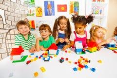Många ungar spelar med plast- kvarter i klassrum Royaltyfri Foto