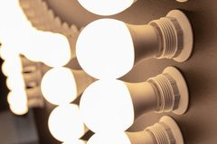 Många vände på, tända kulor med lamphållare tätt upp arkivfoton
