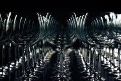 Många vinexponeringsglas i rader för en festlig matställe mot mörka lodisar Royaltyfria Bilder