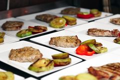 Många vita keramiska fyrkantiga plattor med grillade köttbiffar och Co arkivfoton