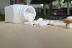 Många vita preventivpillerar/minnestavlor/medicin på den wood plattan Arkivbilder