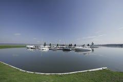 Många yachter på pir på sjön Royaltyfri Bild