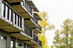 Många yttre svarta balkonger på byggnad från sidan med höstträd i bakgrunden arkivfoton