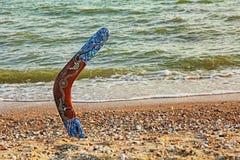 Mångfärgad australisk bumerang på den sandiga kustlinjen nära havet su Royaltyfri Fotografi