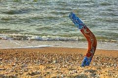 Mångfärgad australisk bumerang på den sandiga kustlinjen nära havet su Royaltyfri Foto