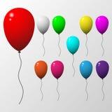 Mångfärgad ballonguppsättning med grå bakgrund Arkivbild