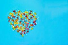 Mångfärgad hjärta formade godisar med elektrisk blå bakgrund arkivbild
