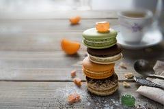 Mångfärgad lögn för makaroni på en trätabell med olika ingredienser, med torkade aprikors, tangerin och sötsaker royaltyfria foton