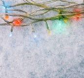 Mångfärgad ljusgirland på den vita snön Royaltyfri Fotografi