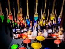 Mångfärgad målarfärg på burk och skedar garnering Royaltyfri Fotografi