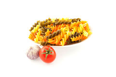 Mångfärgad pasta, en tomat och vitlök Fotografering för Bildbyråer