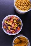 Mångfärgad pasta med tillägget av naturlig grönsakfärg I en krus på en svart konkret tabell Bästa sikt, kopieringsutrymme royaltyfria foton