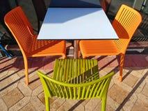 Mångfärgad plast- tabell och stolar Restaurangmöblemang Arkivbild