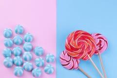 Mångfärgad rund godis och kulöra klubbor på rosa färger och en blå ljus bakgrund Arkivfoto