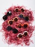 mångfärgad solglasögon på rosa pappers- rester royaltyfria bilder