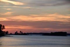 Mångfärgad solnedgång på den blåa sjön till och med trädkontur Royaltyfri Foto