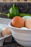 Mångfärgade ägg och Veggies i ett kök royaltyfria bilder