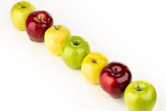 Mångfärgade äpplen i rad på en vit tabell Arkivfoto