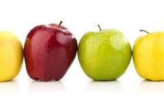 Mångfärgade äpplen i rad på en vit tabell Royaltyfria Bilder
