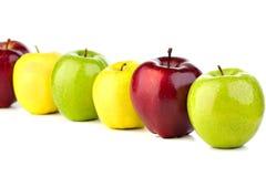 Mångfärgade äpplen i rad på en vit tabell Arkivfoton
