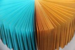 Mångfärgade ark av papper för att anteckna anmärkningar på en turkos och en guling för plan yttersida Arkivbild