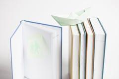 Mångfärgade böcker med det pappers- fartyget Arkivbilder