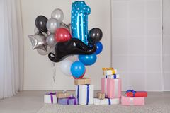 Mångfärgade ballonger och gåvor i vitt rum fotografering för bildbyråer