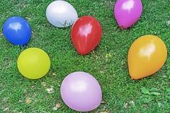Mångfärgade ballonger på grönt gräs Bakgrund av kulöra ballonger arkivbild