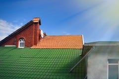 Mångfärgade belade med tegel tak av hus mot den blåa himlen med molnbakgrundslofter apelsin och solstrålar för grön färg arkivfoton