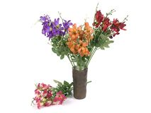 Mångfärgade blommor i en vas som isoleras på vit bakgrund Arkivfoto