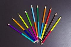 Mångfärgade blyertspennor för att dra på en svart bakgrund idérikt begrepp Arkivbilder