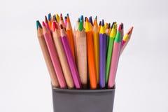 Mångfärgade blyertspennor i den svarta asken på en vit bakgrund tillbaka begreppsskola till Arkivbild