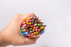 Mångfärgade blyertspennor i manhanden på en vit bakgrund tillbaka begreppsskola till Arkivbild