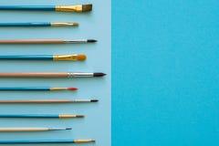 Mångfärgade blyertspennor och borstar på det blåa papperet tillbaka skola till Royaltyfri Foto