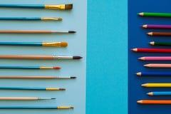 Mångfärgade blyertspennor och borstar på det blåa papperet tillbaka skola till Arkivbilder