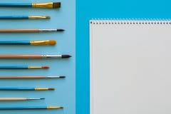 Mångfärgade blyertspennor och borstar på det blåa papperet tillbaka skola till Royaltyfri Fotografi