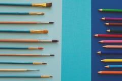 Mångfärgade blyertspennor och borstar på det blåa papperet tillbaka skola till kopiera avstånd Top beskådar Lekmanna- lägenhet to Arkivfoton