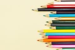 Mångfärgade blyertspennor på en pastellfärgad gul bakgrund, utrymme för text royaltyfri bild