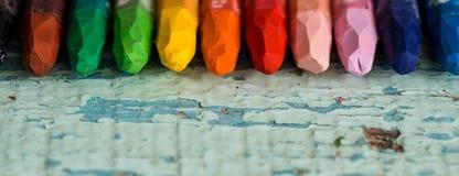 Mångfärgade blyertspennor som en regnbåge på valentin \ 's-dag på en trätabell Två röda hjärtor på papper Kopieringsutrymme, bäst arkivbilder