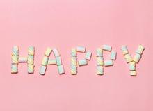 Mångfärgade bokstäver som ÄR LYCKLIGA från marshmallowen på försiktig rosa bakgrund Lekmanna- lägenhet Bild för valentindagbegrep Arkivfoto