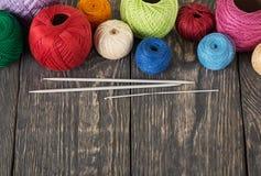 Mångfärgade bollar av bomull dragar för handarbete, på träyttersida royaltyfria foton