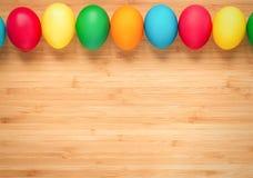 Mångfärgade easter ägg på en ljus träbakgrund Ägg från Arkivbild