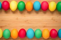Mångfärgade easter ägg på en ljus träbakgrund Ägg på t Arkivbild