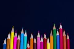 Mångfärgade färgpennor på en svart bakgrund Arkivbild